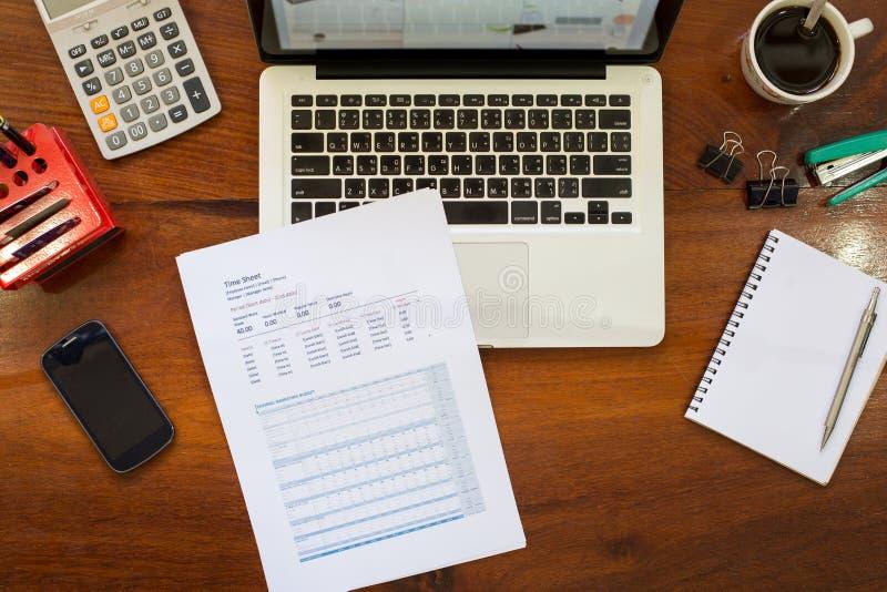 在葡萄酒木桌面上的膝上型计算机在有accessori的现代办公室 免版税图库摄影