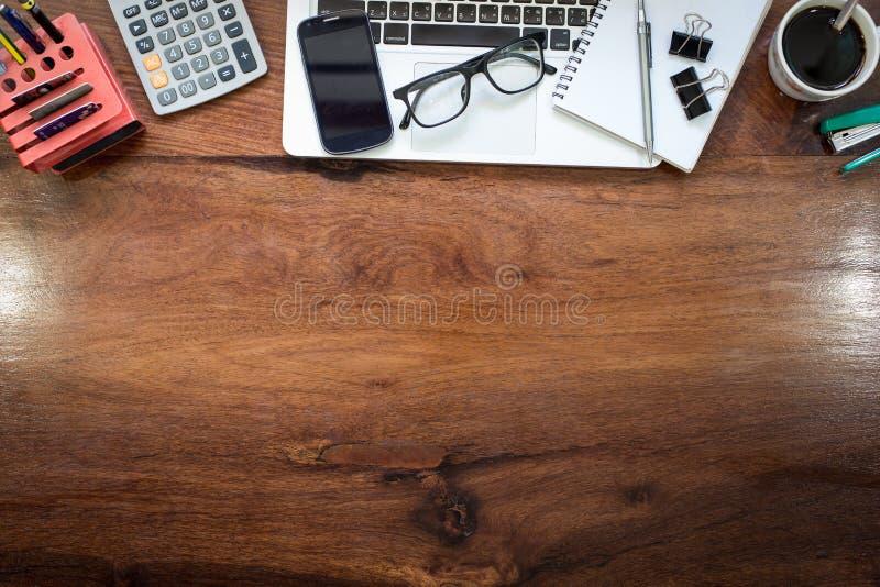 在葡萄酒木桌面上的膝上型计算机在有accessori的现代办公室 免版税库存图片