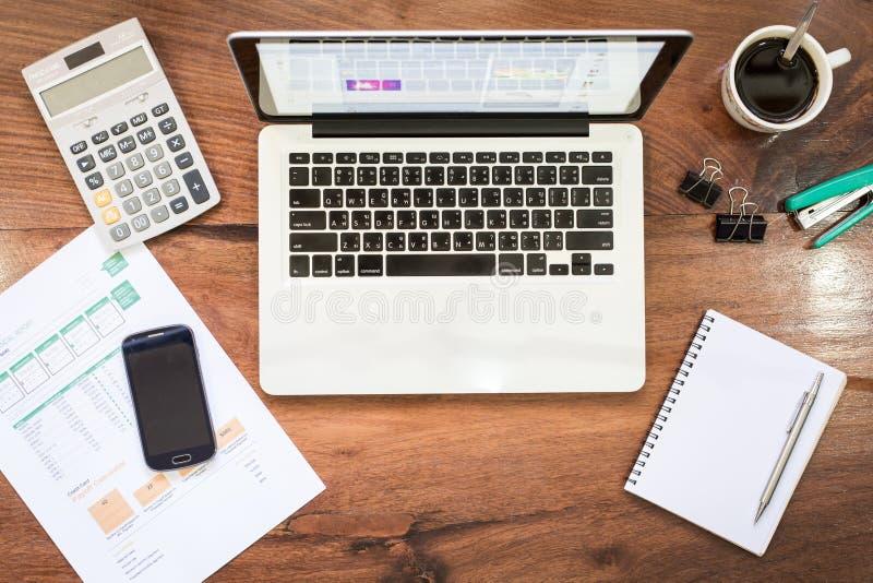 在葡萄酒木桌面上的膝上型计算机在有accessori的现代办公室 库存照片