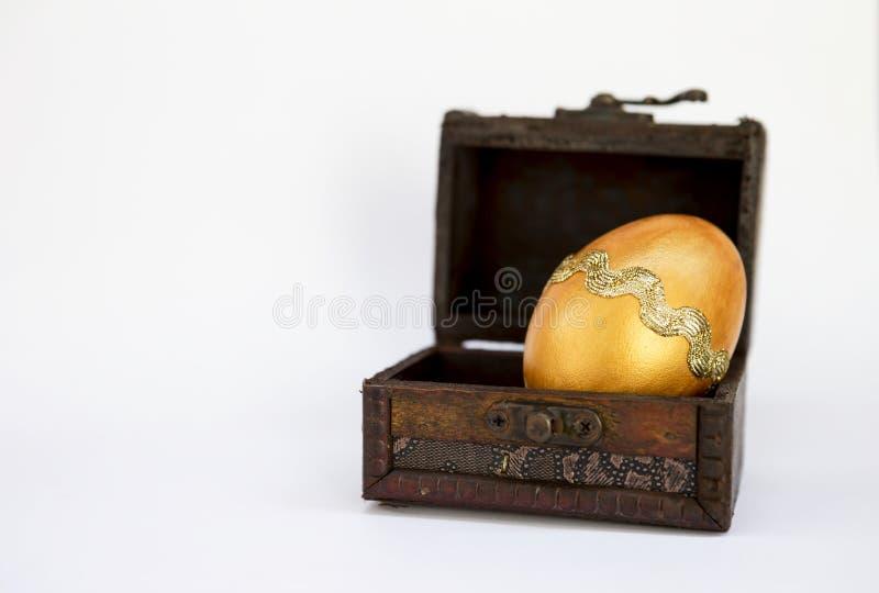 在葡萄酒木箱的金黄设计复活节彩蛋 图库摄影