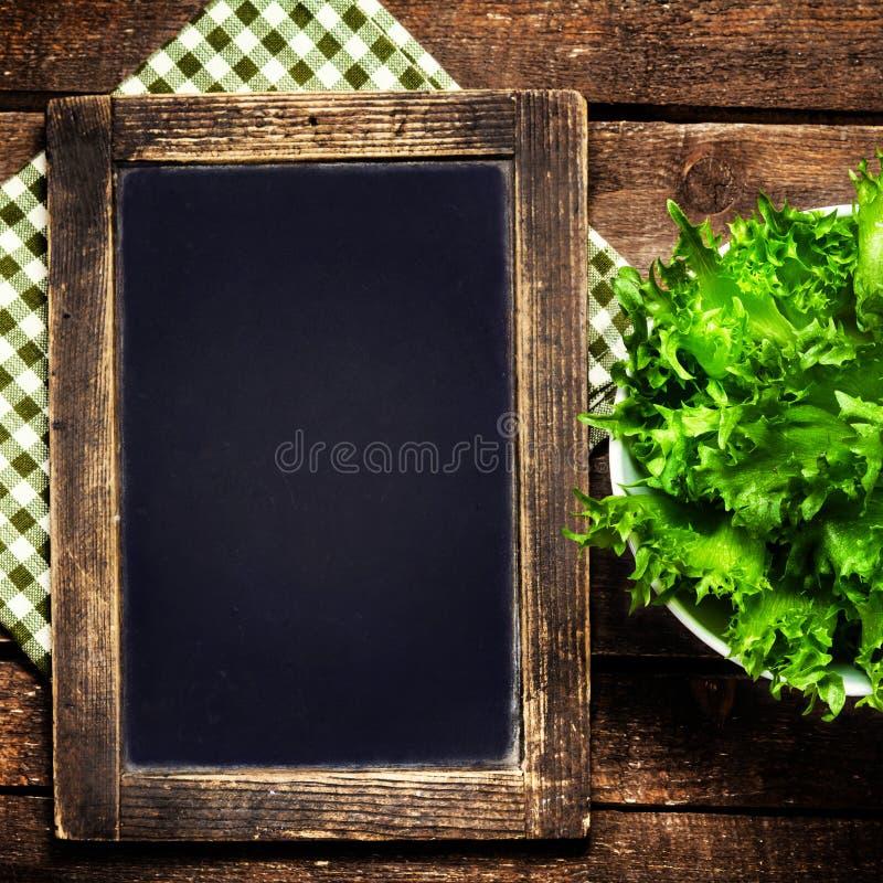 在葡萄酒木背景的空白的菜单黑板与绿色 库存图片