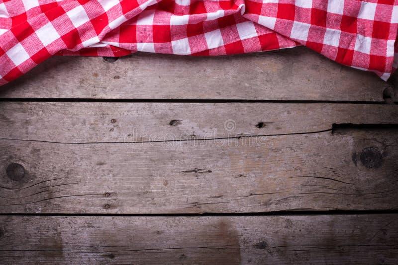 在葡萄酒木背景的红色方格的洗碗布 库存图片