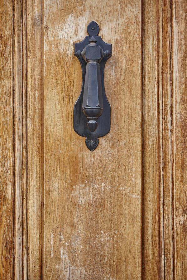 在葡萄酒木门的古色古香的金属门把 装饰 库存照片