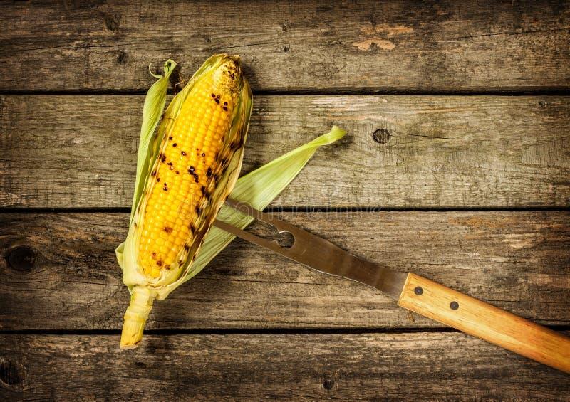 在葡萄酒木头背景的烤玉米棒子 免版税库存照片