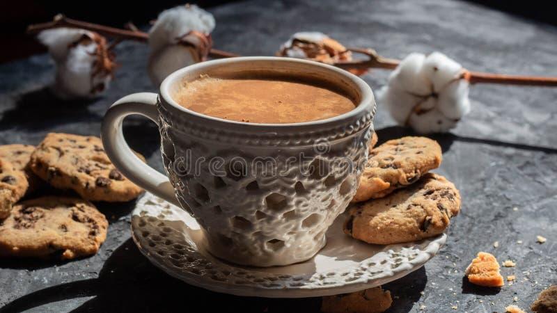 在葡萄酒杯子的芬芳咖啡用在黑背景的曲奇饼 从窗口的自然光 r 免版税库存照片