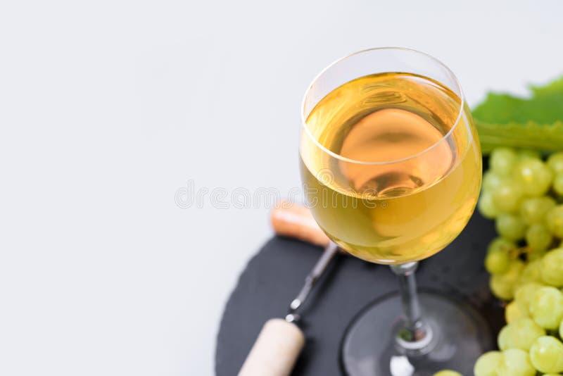 在葡萄酒杯的顶视图白酒用葡萄、黄柏和拔塞螺旋在灰色背景 假日庆祝概念 库存图片