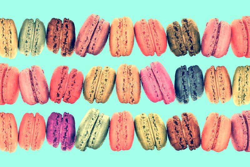 在葡萄酒柔和的淡色彩背景的五颜六色的行macarons 库存照片