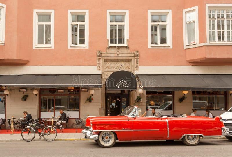 在葡萄酒样式的卡迪拉克敞蓬车红色汽车停放了有松弛游人的过去旅馆 免版税库存照片