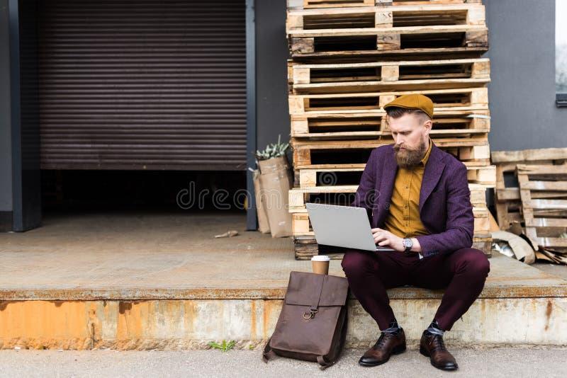 在葡萄酒样式的英俊的商人给研究膝上型计算机穿衣 库存图片