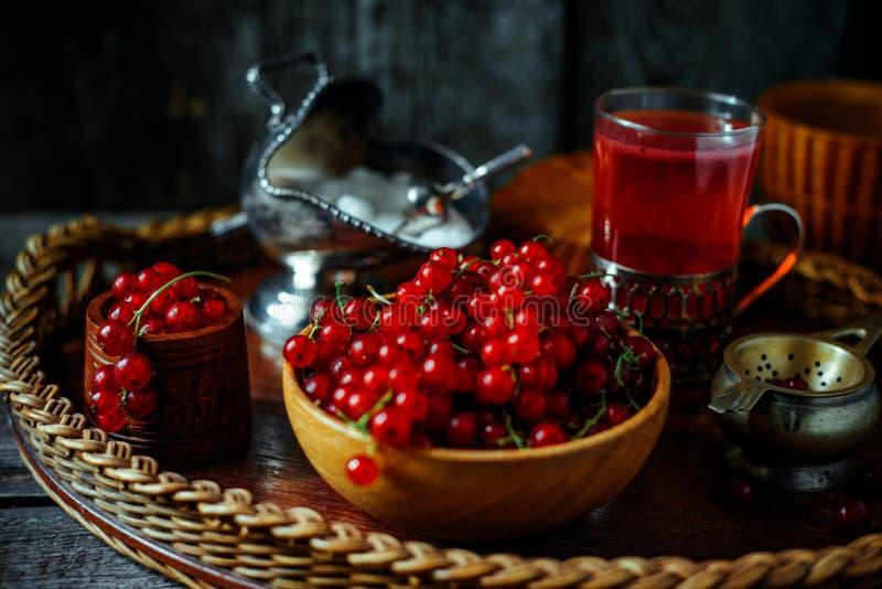 在葡萄酒样式的静物画 关闭有红色潮流的木碗和茶或者果子饮料 免版税库存照片