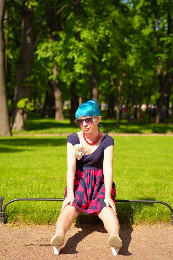 在葡萄酒样式衣物的画报少妇巫婆蓝色头发在城市公园 库存图片