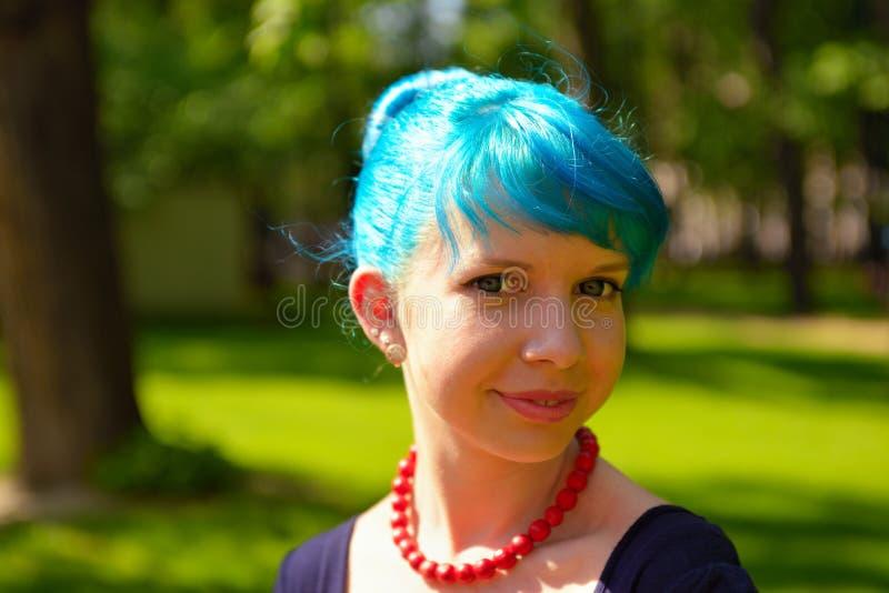 在葡萄酒样式衣物的画报少妇巫婆蓝色头发在城市公园 库存照片