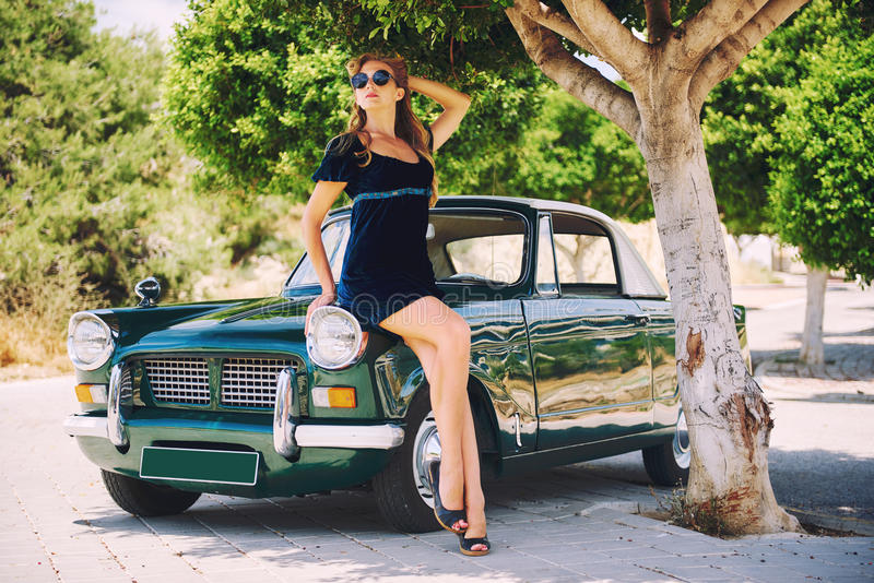 在葡萄酒汽车附近的妇女姿势 免版税库存图片