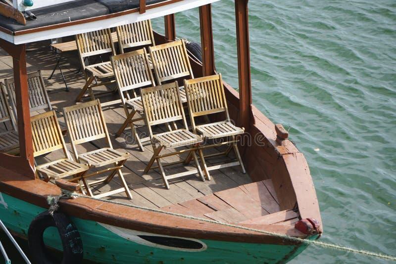 在葡萄酒游览小船的甲板的木椅子在会安市,越南附近的 库存照片