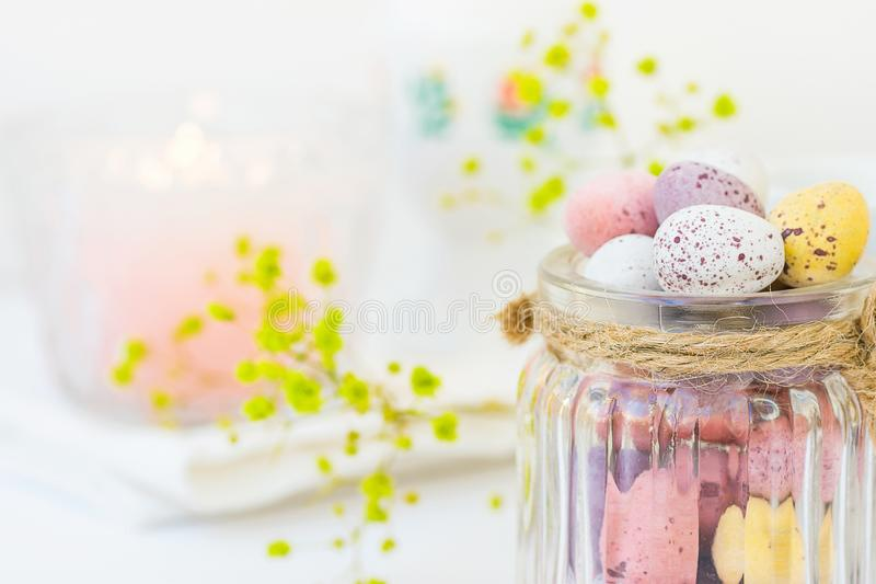 在葡萄酒玻璃瓶子的巧克力糖多彩多姿的小鹌鹑复活节彩蛋淡色在白色木表Yello花 图库摄影