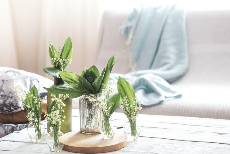 在葡萄酒玻璃瓶的白色春天花snowdrops在白色木桌,村庄室内装饰上 免版税库存图片