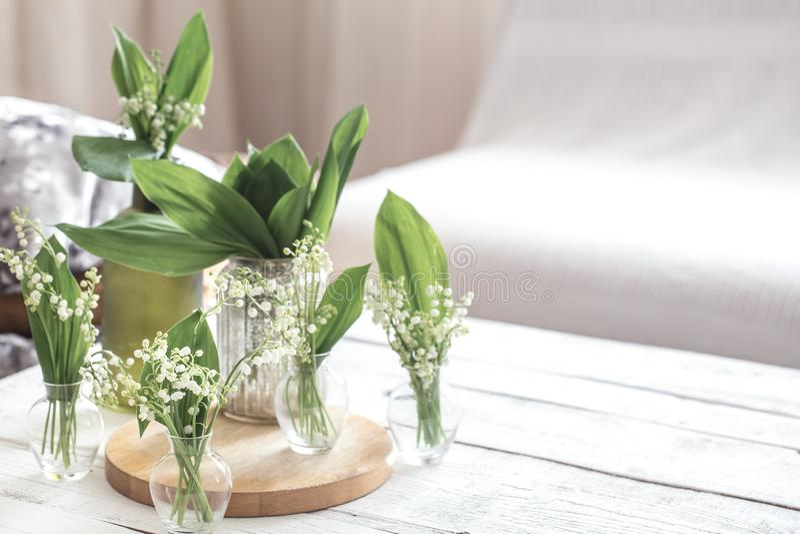 在葡萄酒玻璃瓶的白色春天花snowdrops在白色木桌,村庄室内装饰上 免版税库存照片