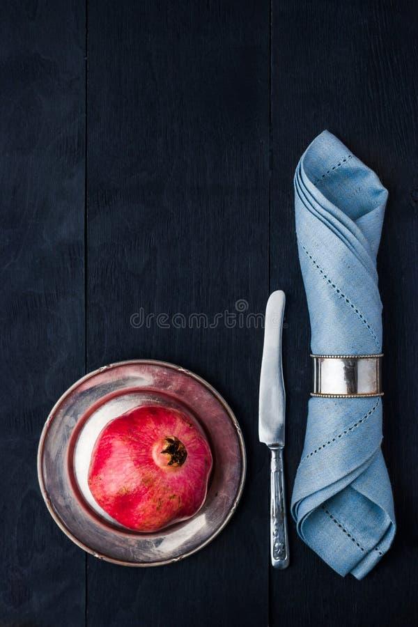 在葡萄酒的石榴金属片与刀子和餐巾垂直 免版税库存照片