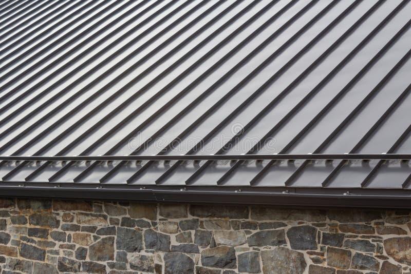在葡萄酒石墙的站立的缝现代金属屋顶 库存图片