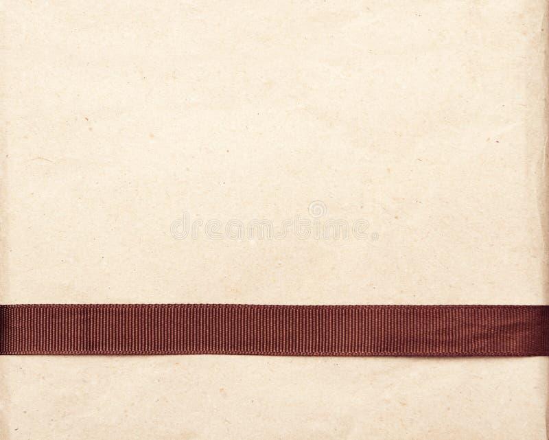 在葡萄酒礼品老纸背景的布朗丝带 免版税库存图片
