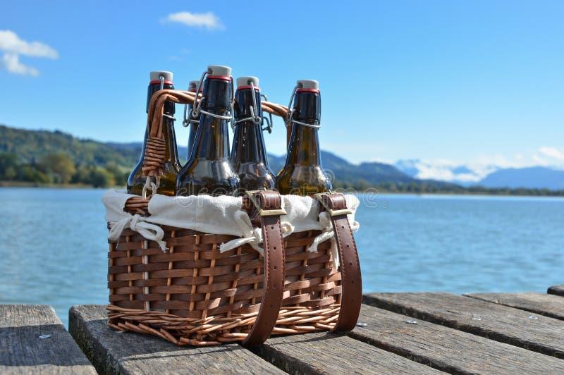在葡萄酒篮子的啤酒瓶 库存照片