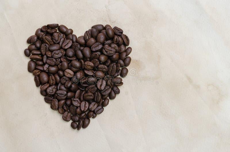 在葡萄酒纸的心形的烤咖啡豆构造背景 图库摄影