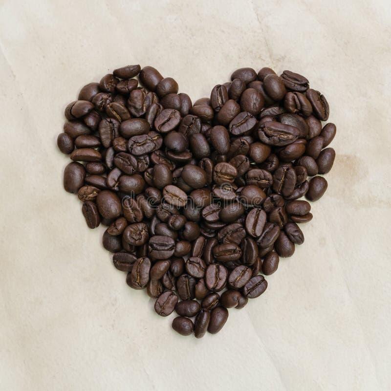 在葡萄酒纸的心形的烤咖啡豆构造backg 免版税库存照片
