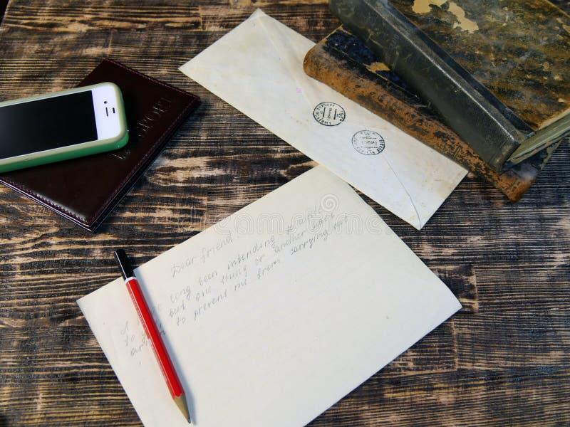 在葡萄酒背景的老信件与现代电话 库存照片