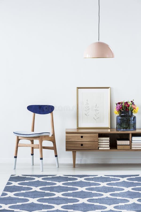 在葡萄酒蓝色客厅内部的被仿造的地毯与椅子 免版税库存图片