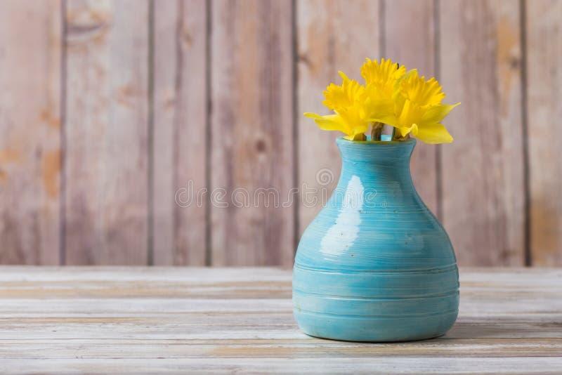 在葡萄酒蓝色瓦器花瓶的黄水仙 免版税图库摄影