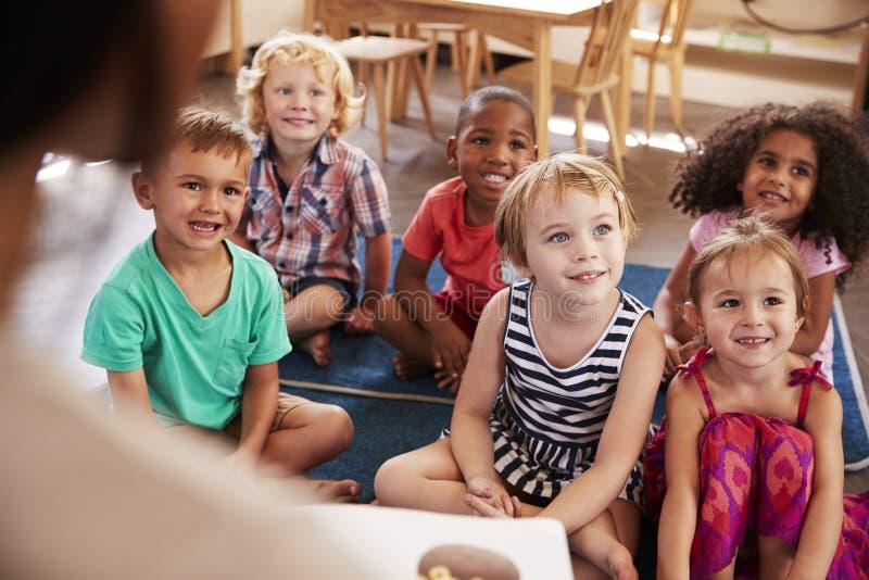 在蒙台梭利学校读对孩子的老师在故事时间 免版税库存图片