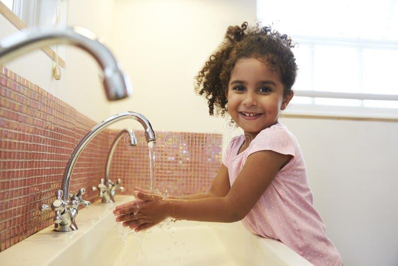 在蒙台梭利学校洗涤的手的母学生在洗手间 免版税库存图片