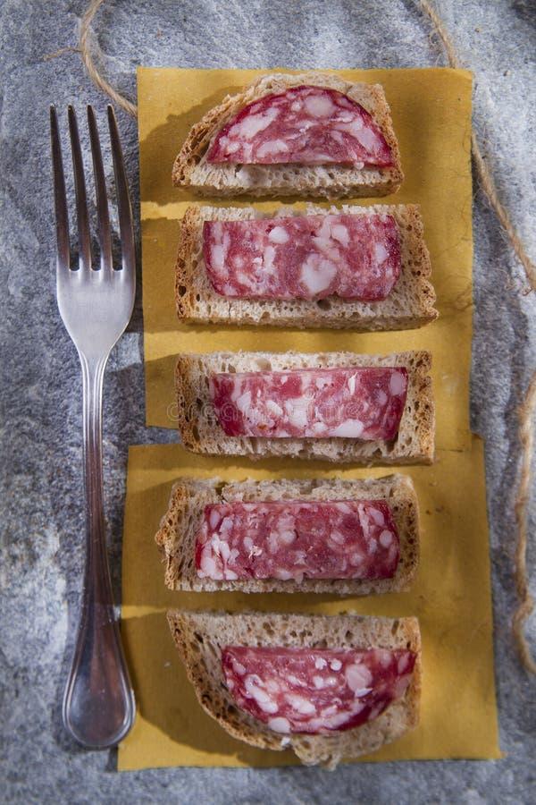 在蒜味咸腊肠上添面包 免版税库存图片