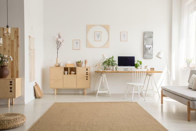 在蒲团和灰色沙发之间的布朗地毯在白色家庭办公室int 免版税库存图片