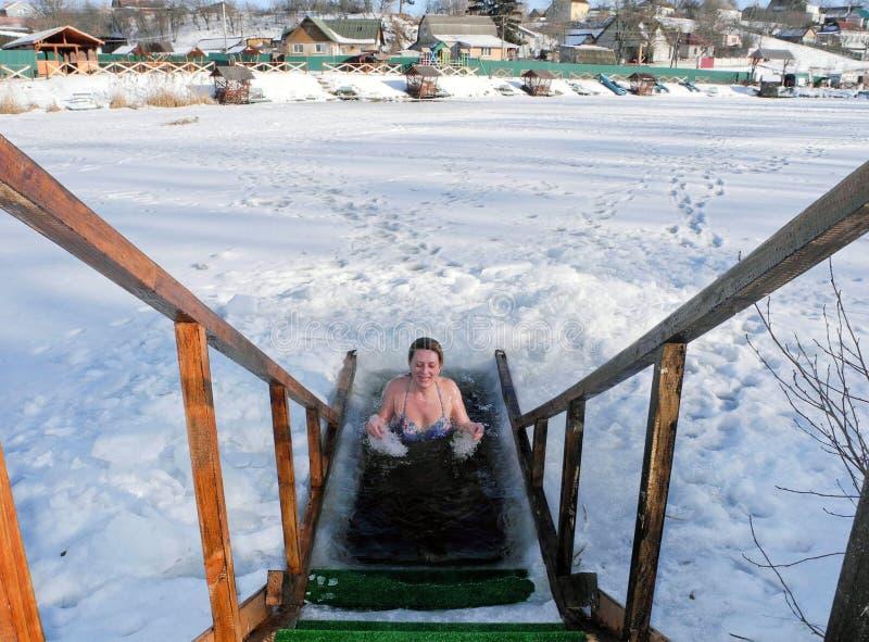 在蒸汽浴以后冰在冬天冰孔的游泳 库存照片