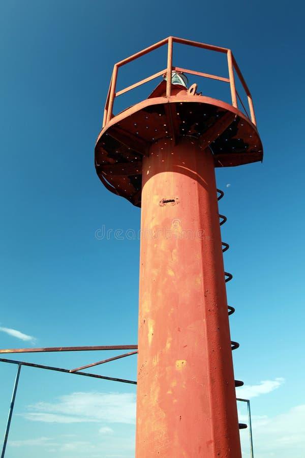 在蓝天上的小红色灯塔杆 库存图片