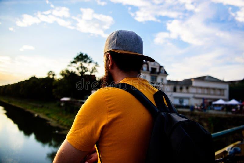 在蓝天前面的人在晚上时间敬佩风景 享受宜人的片刻 盖帽的人享受日落,当立场时 免版税图库摄影