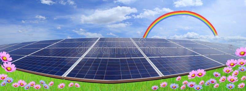 在蓝天和彩虹的太阳电池板与花的领域 免版税库存照片