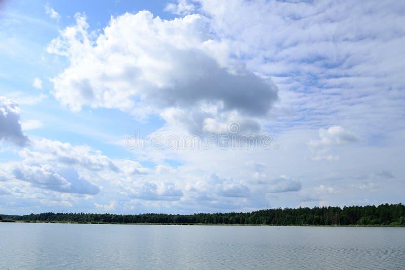 在蓝天的云彩在湖在夏天 图库摄影