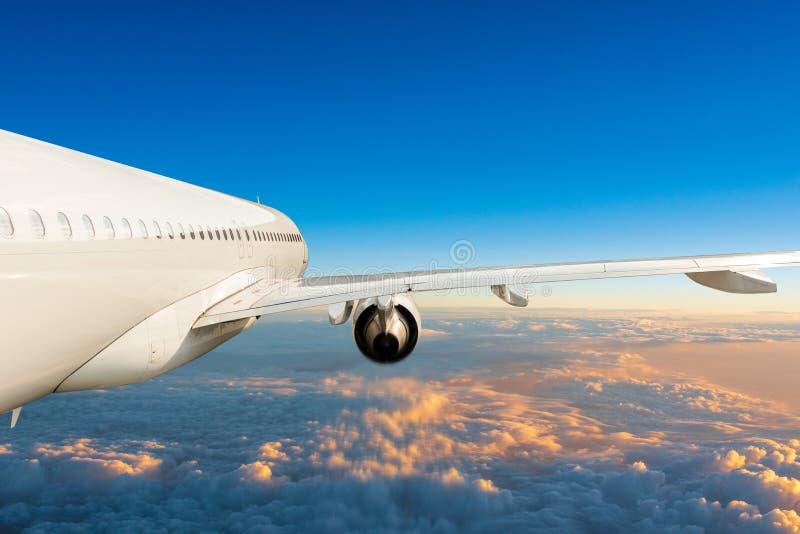 在蓝天的喷气式客机飞机,独特的侧视图 在积云上的航空器飞行 飞机旅行概念 免版税库存图片