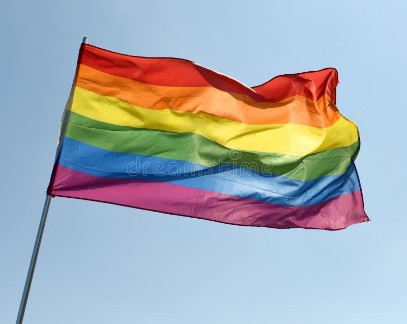 在蓝天的彩虹旗子 免版税库存照片