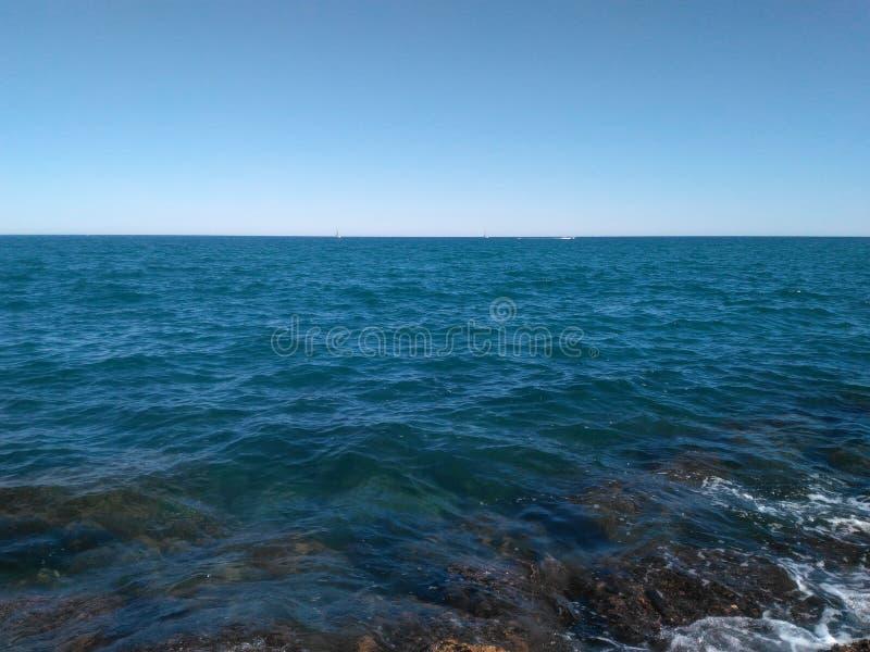 12 66 4000 01在蓝天的深刻的蓝色海背景 免版税库存照片