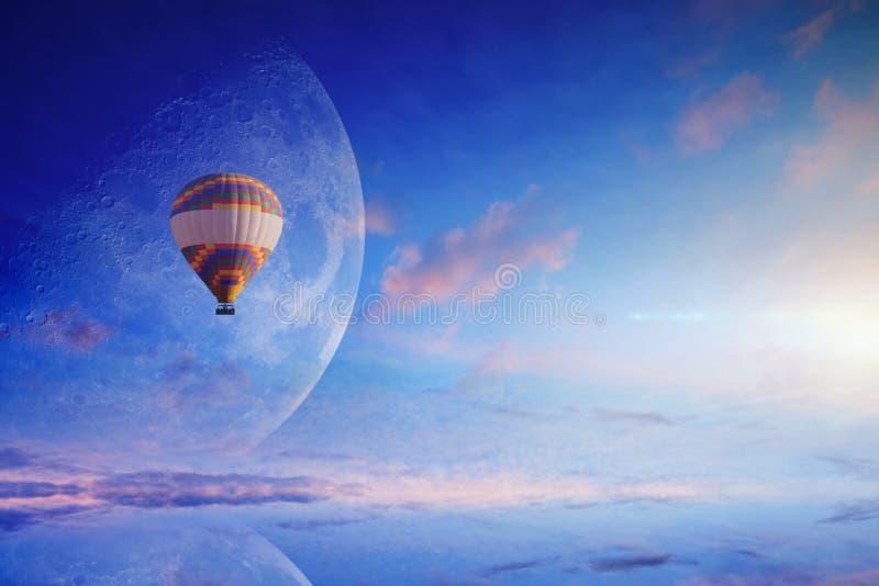 在蓝天的热空气气球与上升的满月 库存照片