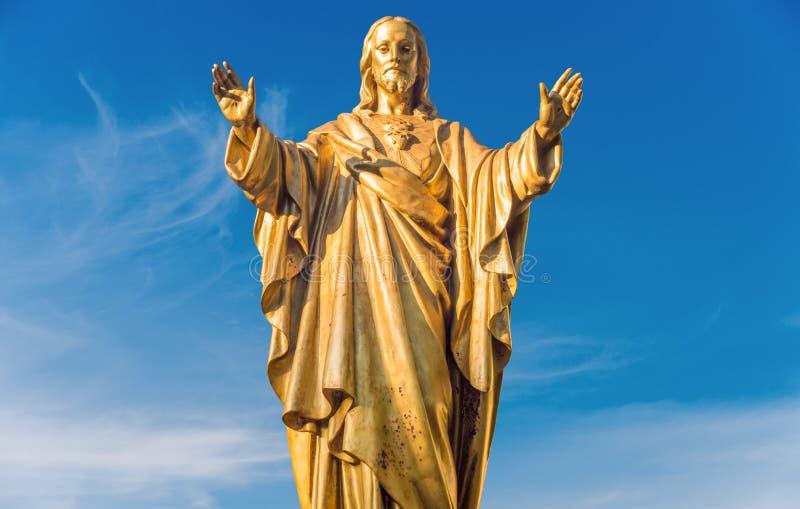 在蓝天的耶稣基督金黄雕象 免版税库存图片