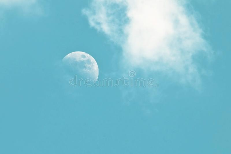 在蓝天的苍白早晨月亮与云彩 免版税库存照片
