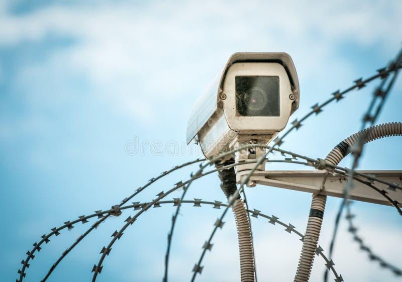 在蓝天的观察照相机和barbwire。 免版税图库摄影