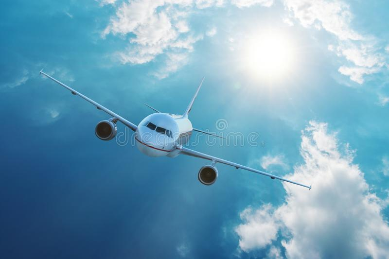 在蓝天的飞机飞行与云彩 旅行和运输概念 库存照片