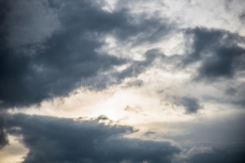 在蓝天的黑暗的云彩形成在日落前的晚上 库存照片