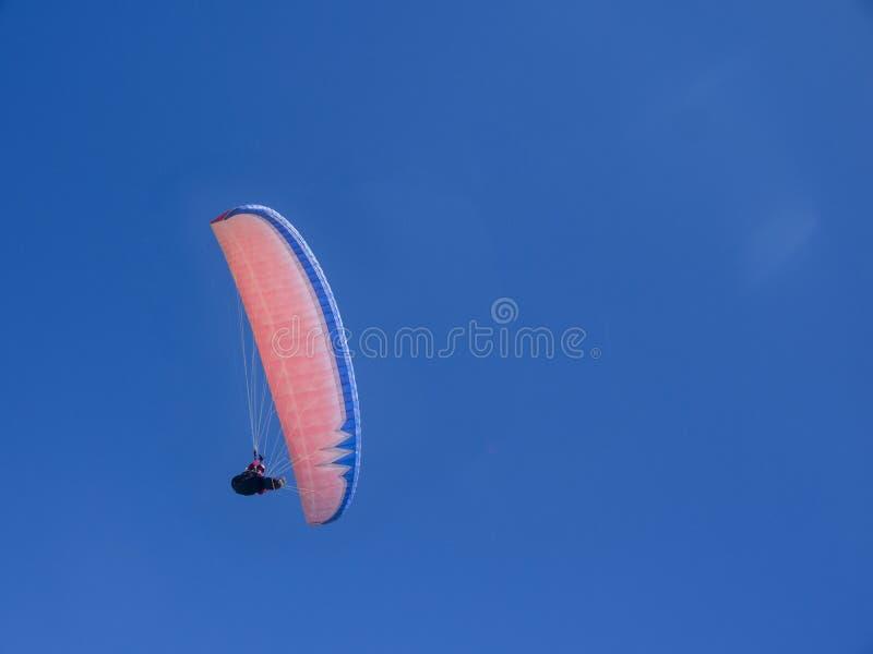在蓝天的滑翔伞红色飞行 免版税图库摄影
