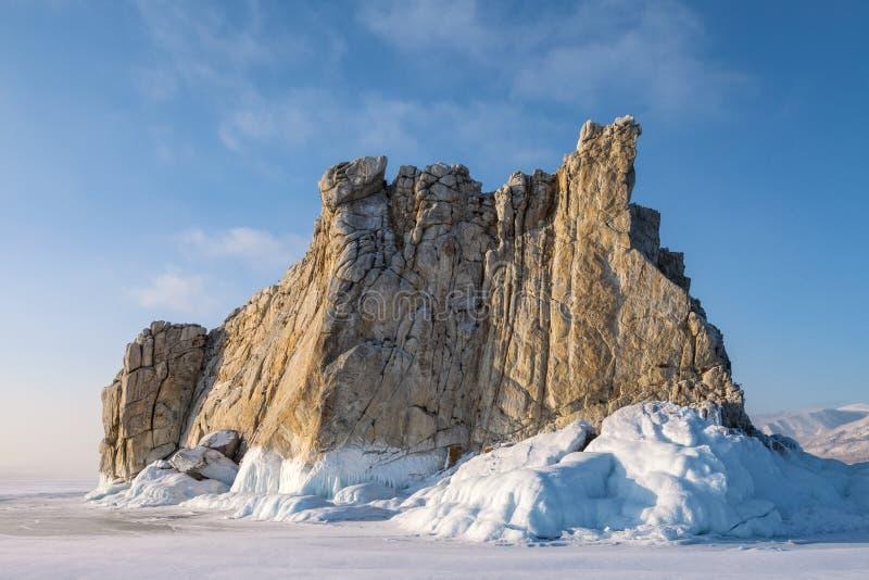 在蓝天背景的冰围拢的岩石 免版税库存图片